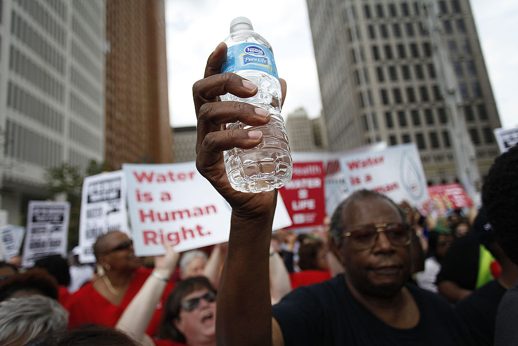 water bottle held up at 2014 protest for water rights in Detroit