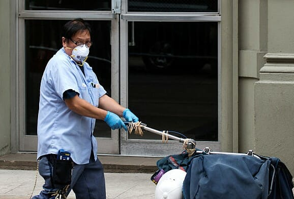 Postal worker wearing a mask and gloves while delivering mail
